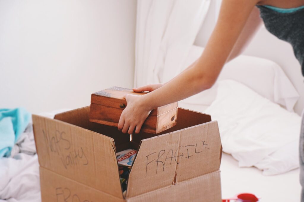 Girl packing a box for moving 