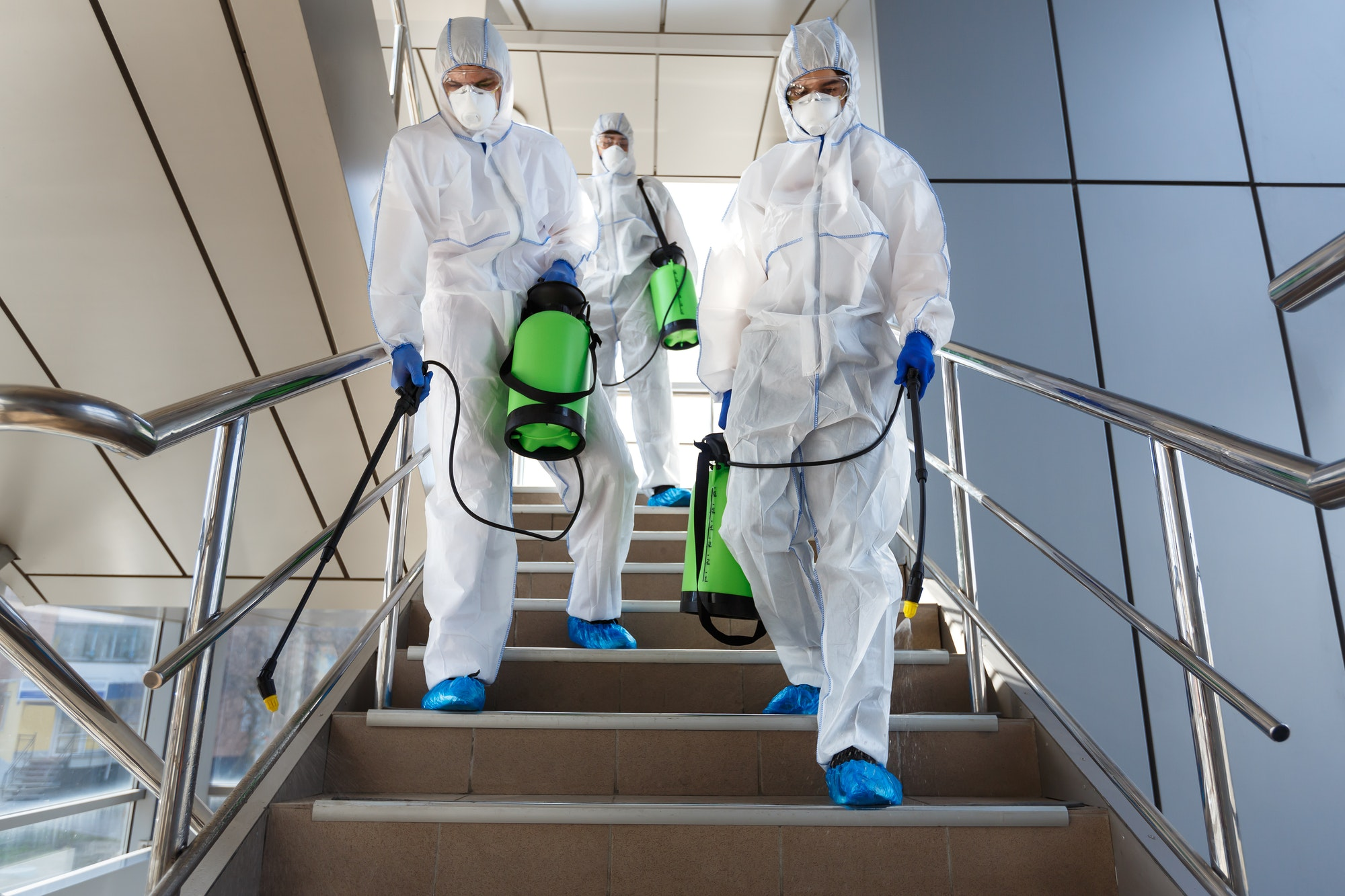 People wearing protective suits disinfecting stairs with spray