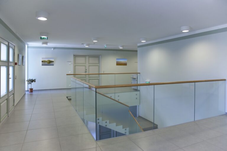 Stairwell and open plan room with large windows and light airy feel, glass balustrade.