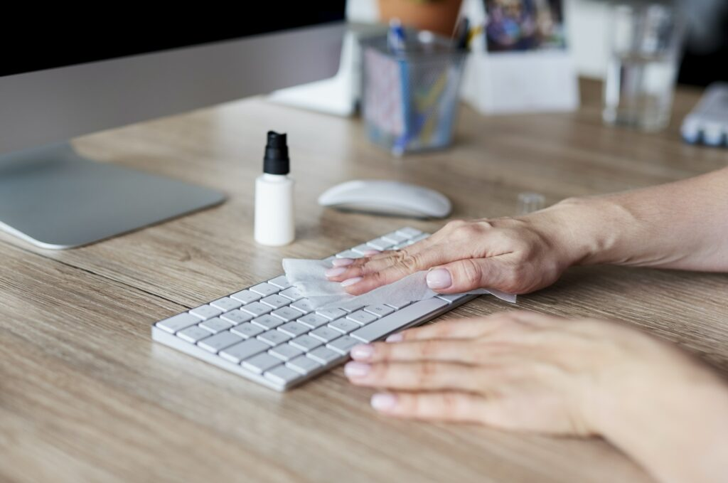 Woman cleaning keyboard in the office